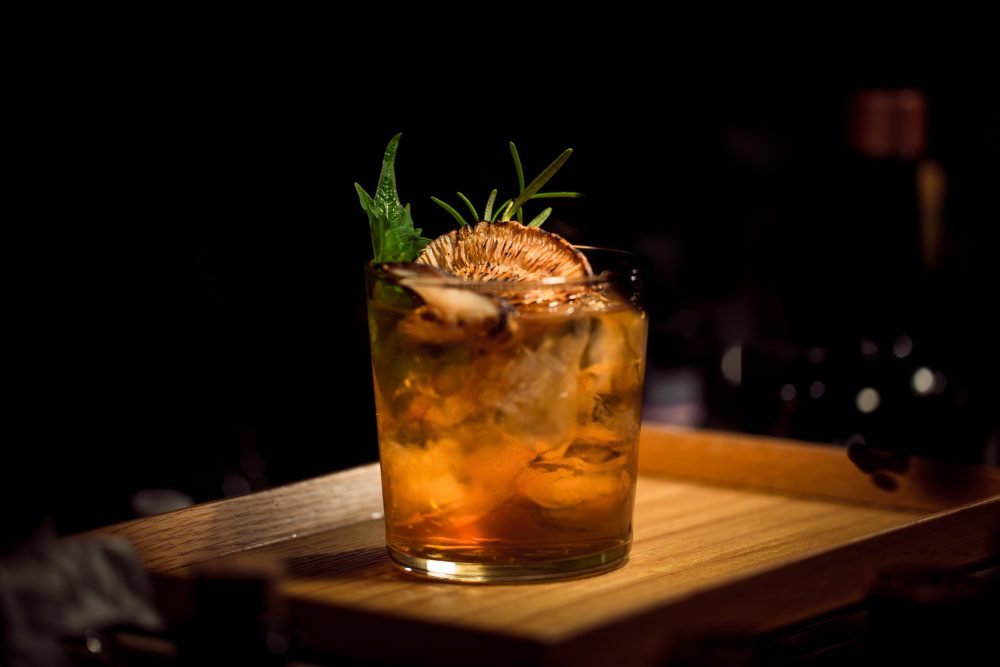 bourbon based cocktail with passionfruit garnish basthed in light on wooden board