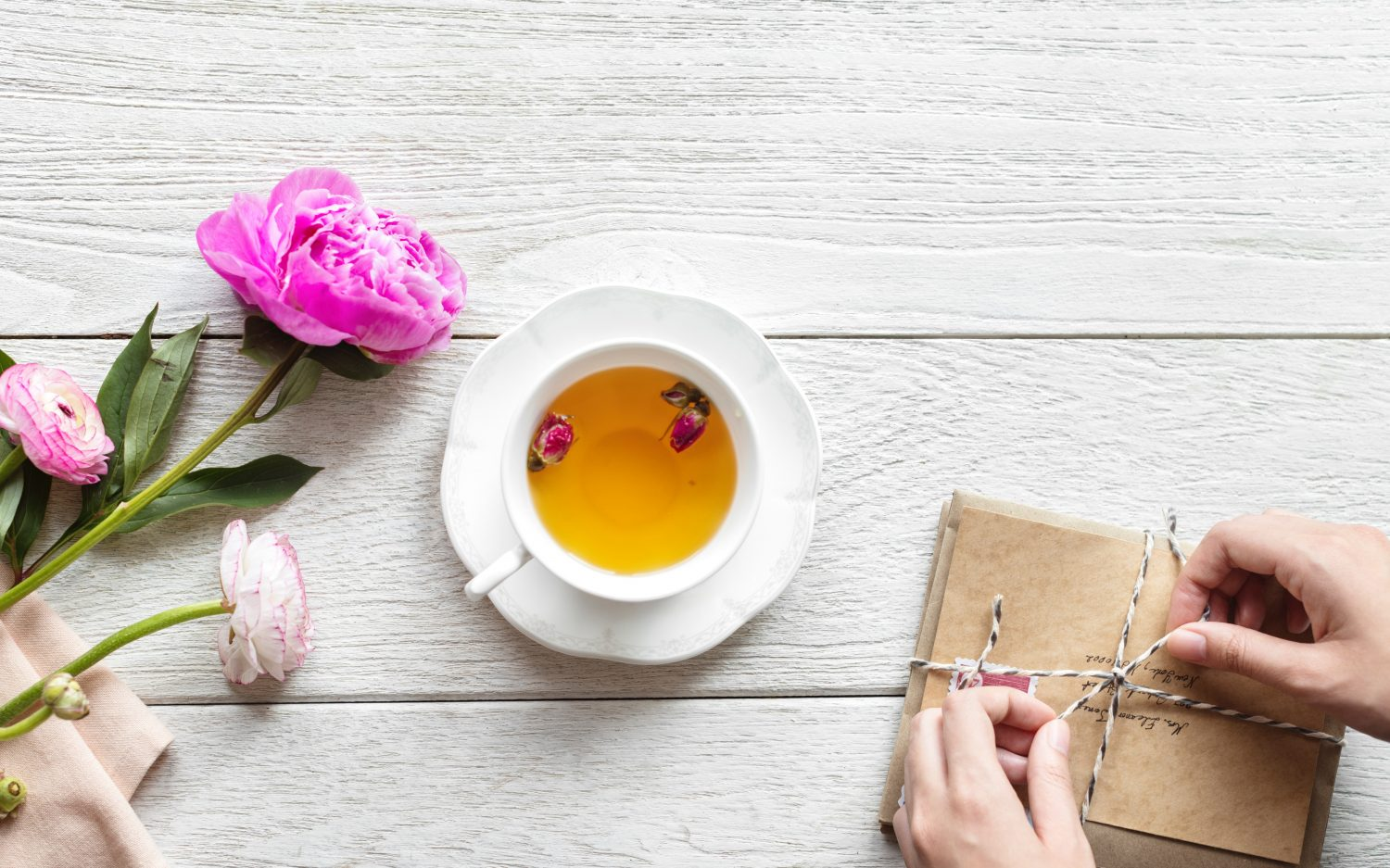 china cup of tea on white wooden table with pink carnation lying next to it